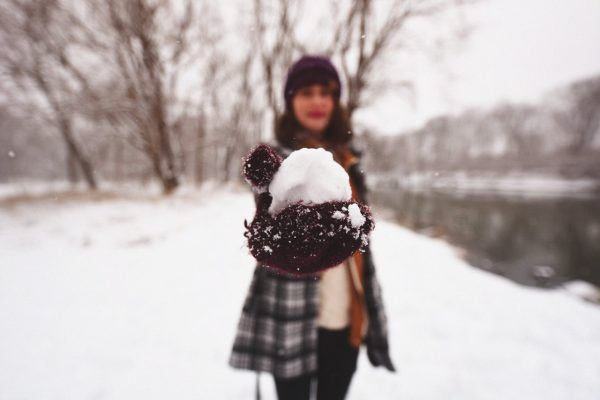 Woman outside holding snowball to symbolize snowball effect
